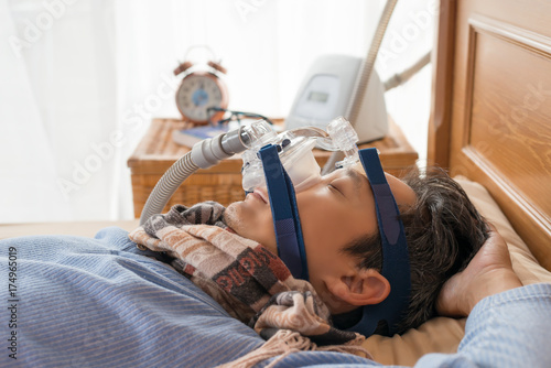 Man laying in bed wearing CPAP mask ,healthcare concept Poster