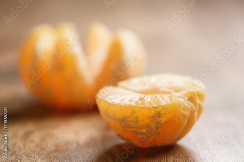 open peeled tangerine on old wood table - 174965870
