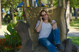 The girl in the decorative chair. A girl in glasses sits a carved stump and climbs into the smartphone. A woman is sitting in a carved wooden chair and talking on the phone. - 174966839