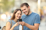Happy couple using a smart phone on the street - 174968694