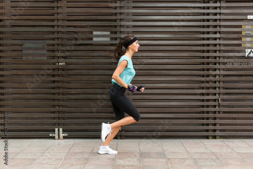 Poster Jogging Side view of sporty young woman running on a sidewalk.
