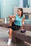 Young fitness woman resting after exercising, sitting at the bench in city center. - 174973428
