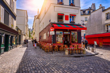 Cozy street with tables of cafe in quarter Montmartre in Paris, France