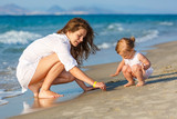Mother and little daughter playing on the beach - 174988670
