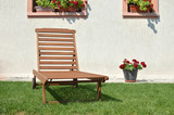 Wooden deck chair on a garden lawn in front of a white house wall with flowers - 174989088