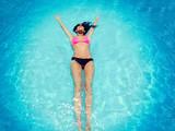Frau kühlt sich im Swimmingpool ab - 174995698