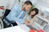 young attractive couple accounting at home - 174998026