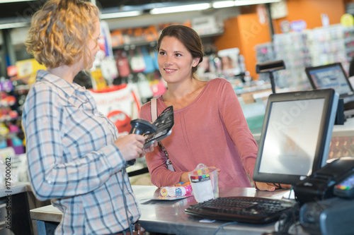 young saleswoman scanning product at checkout counter in store