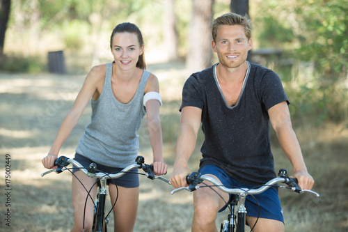 young couple cycling in the forest Poster