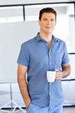 Young businessman in office with a mug - 175003060