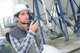 Man in cement factory using walkie talkie - 175004299
