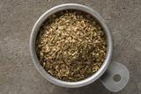 A vintage measuring cup of dried oregano - 175006258