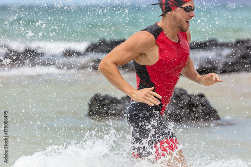 Triathlon swimming man triathlete swimmer running out of ocean finishing swim competition. Fit male athlete ending swimming sprinting out of ocean with water splashing background training for ironman.