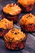 Quadro Orange Halloween cupcakes with black sprinkles on rustic table