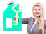 Female hand holding green house model. - 175015614
