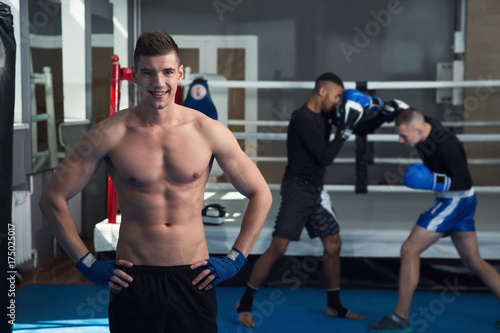 Staande foto Strong man against the backdrop of the boxing ring and training. Boxing Gym.