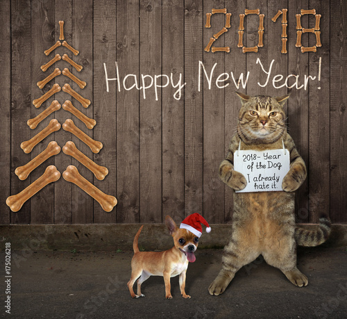 The cat is holding a funny banner . A dog in the santa claus hat is next to him. - 175026218