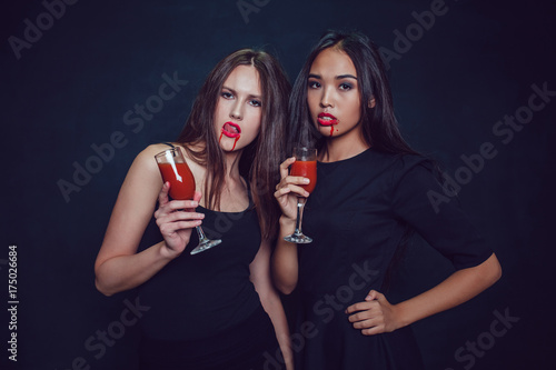 Attractive girls in the image of vampires hold glasses with blood Poster