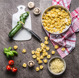 Tortellini with zucchini and vegetarian cooking ingredients on kitchen table background with cutting board and knife, top view. Healthy cooking and eating. Italian food concept - 175030694