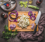 Cooking preparation with vegetables: kohlrabi and leeks on wooden cutting board with knife on rustic background, top view. Healthy vegetarian food and eating, clean or diet nutrition concept - 175030897