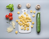 Tortellini with zucchini, mushrooms and vegetarian cooking ingredients on kitchen table background with cutting board , top view, flat lay. Healthy cooking and eating. Italian food concept - 175031461