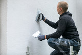 construction worker putting decorative plaster on house exterior - 175035820