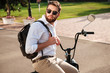 Side view of Calm bearded man in sunglasses with backpack