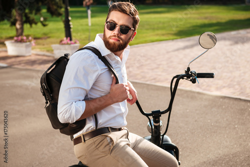 Side view of Calm bearded man in sunglasses with backpack - 175043620
