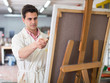 Man near easel painting on canvas - 175044470