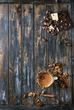 Vintage mug of hot chocolate, decor with nuts, caramel, spices. Ingredients above. Chopped dark and white chocolate, cocoa beans, anise over old wooden table. Top view with space. Dark rustic style - 175044896