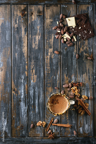 Fotobehang Chocolade Vintage mug of hot chocolate, decor with nuts, caramel, spices. Ingredients above. Chopped dark and white chocolate, cocoa beans, anise over old wooden table. Top view with space. Dark rustic style