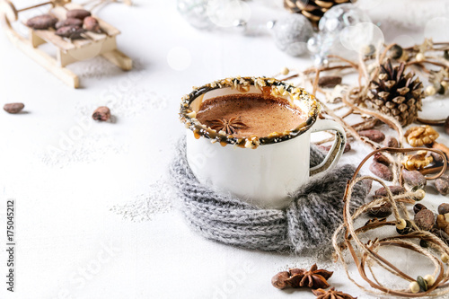 Canvas Chocolade Vintage mug in wool scarf of hot chocolate, decor with nuts, caramel, spices. Ingredients and Christmas toys above over white texture background with space.