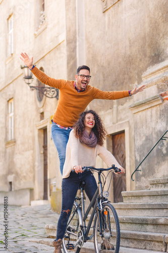 Happy young couple having fun riding a bicycle on sunny autumn day in the city.
