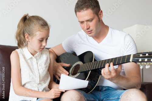 Póster Dad and his daughter compose a song on the guitar.