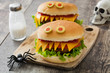 Halloween burger monsters on wooden table