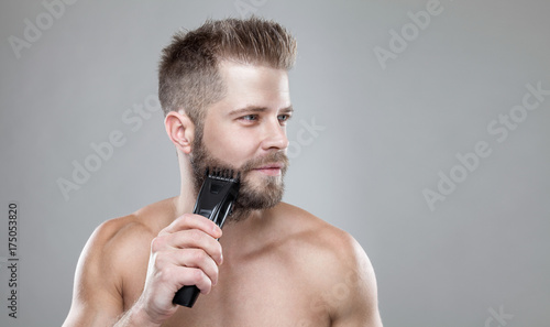 Aluminium Handsome bearded man trimming his beard with a trimmer