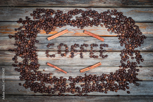An inscription of coffee beans on a wooden table and with cinnamon sticks