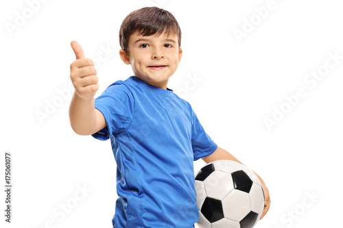 Fotobehang Voetbal Small boy holding football and making thumb up sign