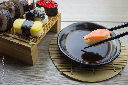 Foto op Canvas Sushi bar Hand using chopsticks pick Sushi,mix sushi,Traditional Japanese cuisine