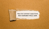 The text When the customer comes first the customer will last appearing behind torn brown paper - 175064469
