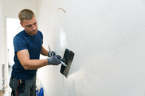 Papiers peints Kiev home improvement - construction worker with plastering tools renovating apartment walls