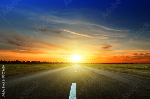 Asphalt road among the fields at sunset