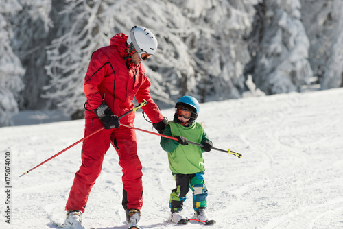 obraz lub plakat Skiing instructor with little boy