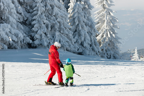 Skiing instructor and child on ski slope