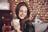 Smiling woman drinking coffee at home - 175075202