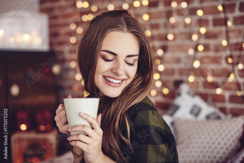Smiling woman drinking coffee at home плакат