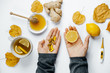 Woman hands with tablets and lemon, tea, thermometer, ginger, honey and dry leaves on a white background. flat lay