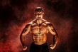 Bodybuilder posing. Fitness tattooed muscled man on red smoke background. Roaring for motivation.
