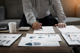 Business man analysed report of profit finance data graph document in his office. - 175087860