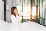 Woman stretching and yawning while waking up in the morning. - 175088401